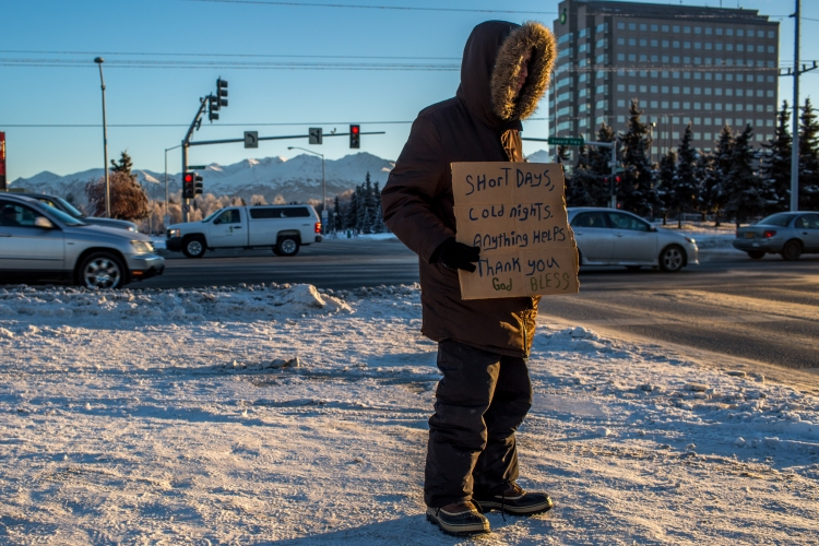 """ANCHORAGE, ALASKA - December 14, 2016: Carl, 28, holds a sign on a corner in Anchorage on the morning December 14, 2016, when the temperature remained in single digits. Carl has been homeless for most of his life. According to him, his 20th anniversary of being homeless is coming up next month, shortly after his birthday. He says physically, the hardest part about being homeless in Anchorage is the frostbite; he typically suffers 5 bouts of frostbite each winter, and is presently suffering his second bout this season. He says he's gotten into cycles in the past of going to jail just to stay warm, which has now made getting work difficult. """"I have 29 misdemeanor thefts, so nobody is going to hire me. So I'm looking for work, but when [employers] get to the computer part, they literally laugh at me and tell me to get out of their store,"""" Carl says. """"I'm not going to lie to nobody; I'm just waiting to die now."""" Emotionally, he says homelessness is very difficult in Anchorage. He says people have spit on him, hit him with rocks, and often treat him like he is not even human. """"I gave up a long time ago,"""" he says. He has two children, ages 8 and 12, but says he doesn't see them. """"I make sure they don't see me,"""" he says./ASH ADAMS"""
